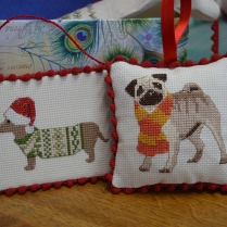 A Christmas dachshund and a cute pug in cross-stitch