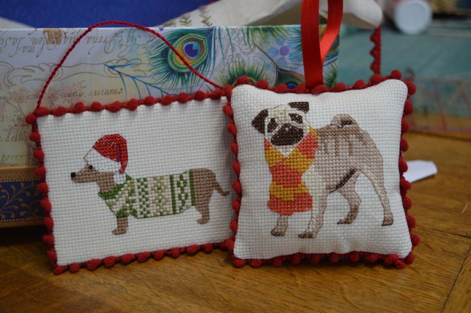 A Christmas dachshund and a cute pug in cross-stitch